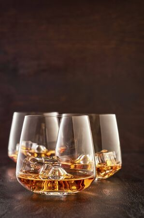 Three crystal glasses of whisky with ice on a wooden table.