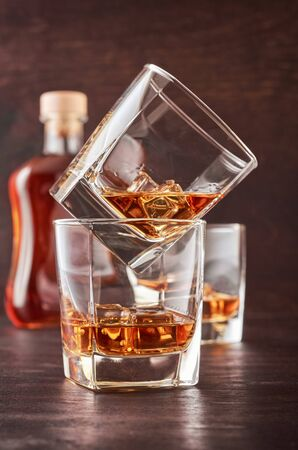 Two glasses of whisky with ice on a wooden table. One glass stands on the other. In the background is a full bottle of whiskey and a glass of whiskey. Stok Fotoğraf