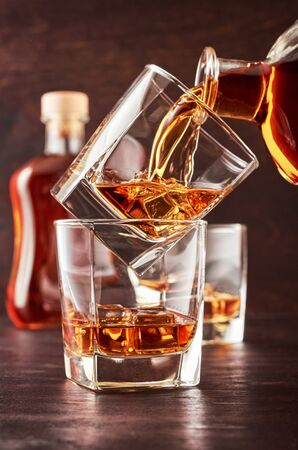 Two glasses of whisky with ice on a wooden table. One glass stands on the other. The glass is poured whiskey from the bottle. In the background is a full bottle of whiskey and a glass of whiskey. Stok Fotoğraf