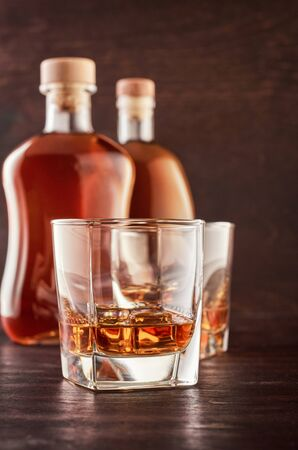 Two glasses of whisky with ice on a wooden table. In the background, two bottles of whiskey of different shapes.