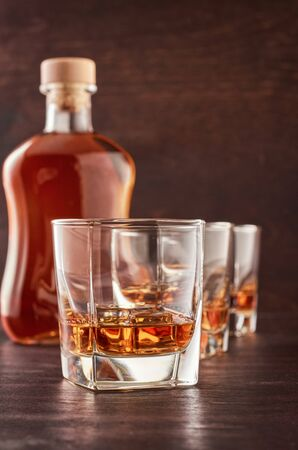 Three glasses of whiskey on the ice on the wooden table. Theres a bottle of whiskey in the background. Stok Fotoğraf