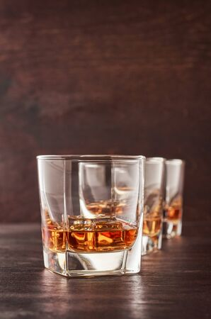 Three glasses of whiskey on the ice on the wooden table.