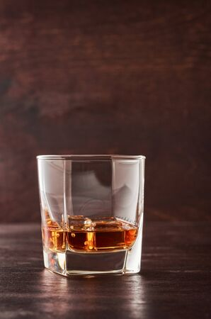 A glass of whisky with ice on a wooden table. Stok Fotoğraf