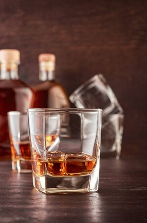 Two glasses of whisky with ice on a wooden table. In the background there are two bottles of whiskey of different shapes and empty glasses for whiskey. Stok Fotoğraf