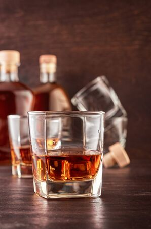 A glass of whiskey with a double portion on a wooden table. In the background, two bottles of whiskey of different shapes, a glass with a portion of whiskey and empty glasses of whiskey. Stok Fotoğraf