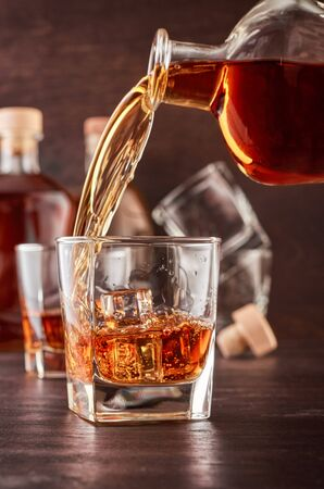 Glass of whiskey on a wooden table, which poured whiskey from a bottle. In the background, two bottles of different shapes, full and empty glasses of whiskey.