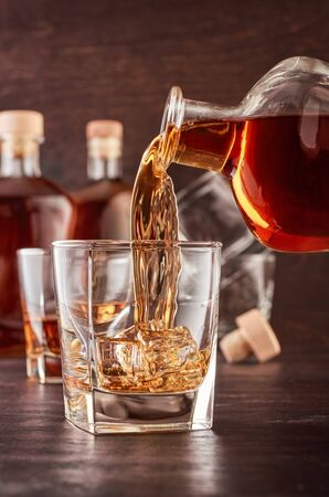 A glass of whiskey on a wooden table. In a glass filled with alcohol from the bottle. In the background, two bottles of whiskey of different shapes, a glass of whiskey and empty glasses of whiskey.