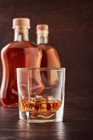 A glass of whisky with ice on a wooden table. In the background, two bottles of whiskey of different shapes. Stok Fotoğraf