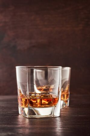 Two glasses of whisky with ice on a wooden table.