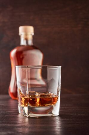 A glass of whisky with ice on a wooden table. Theres a full bottle of whiskey in the background. Stok Fotoğraf