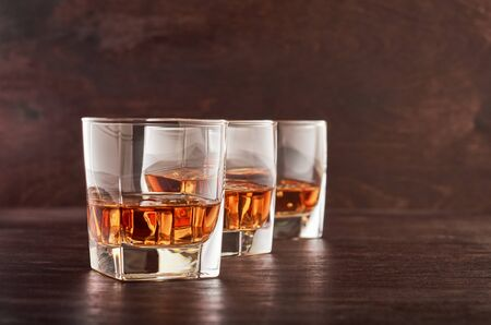 Three glasses of whisky with ice on a wooden table Stok Fotoğraf