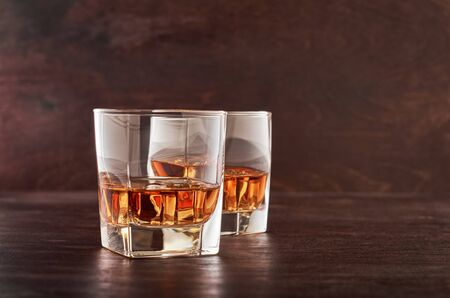 Two glasses of whisky with ice on a wooden table