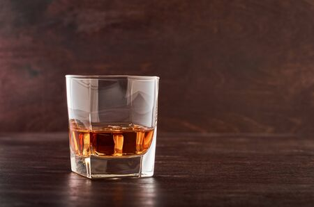 A full glass of whisky with ice on a wooden table Stok Fotoğraf