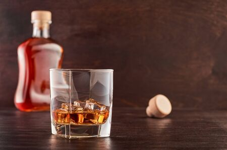 A glass of whisky with ice on a wooden table, a full bottle of whisky in the background