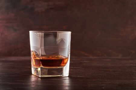 One glass of whiskey on a wooden table