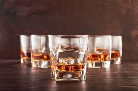 A set of six glasses of whiskey with ice standing on a wooden table. One glass in the foreground, the other glasses in the background with different depth of field. Stok Fotoğraf