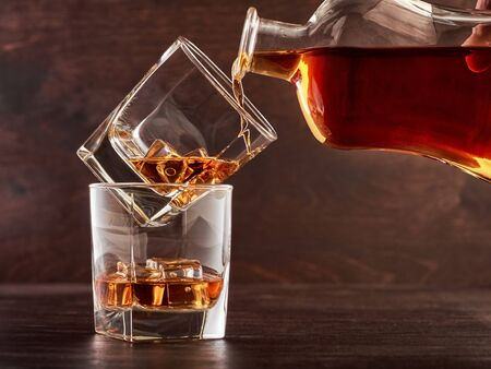 Two glasses of whisky with ice on a wooden table. One glass stands on the other. The glass is poured whiskey from the bottle. Stok Fotoğraf