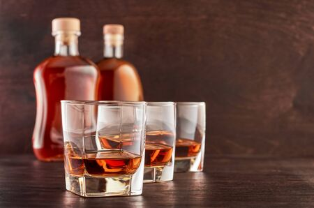 Three glasses of whiskey on a wooden table, two full bottles of whiskey in the background Stok Fotoğraf