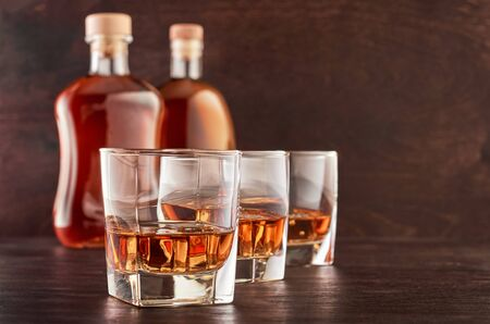 Three glasses of whiskey on ice on a wooden table, two full bottles of whiskey in the background Stok Fotoğraf