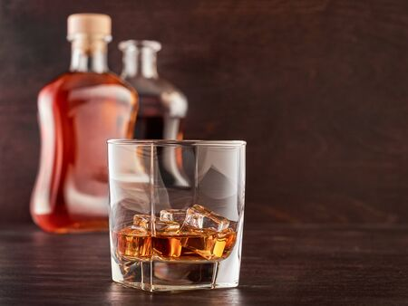 A glass of whisky with ice on a wooden table, two bottles of whisky in the background, full and open