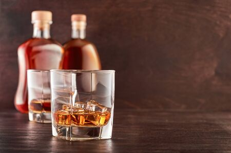 Two glasses of whiskey with ice on a wooden table, in the background two bottles of whiskey of different shapes Stok Fotoğraf