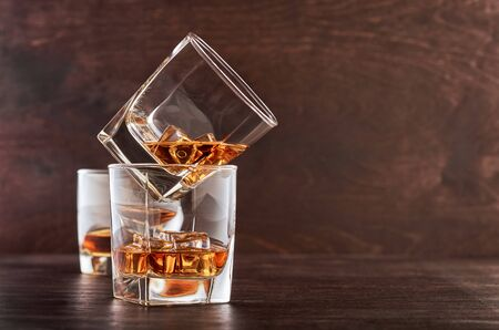 Two glasses of whisky with ice on a wooden table. One glass stands on the other. In the background, a glass of whiskey