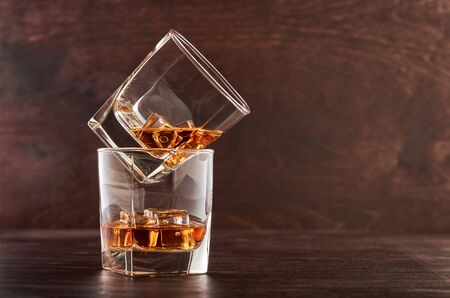 Two glasses of whisky with ice on a wooden table. One glass stands on the other.
