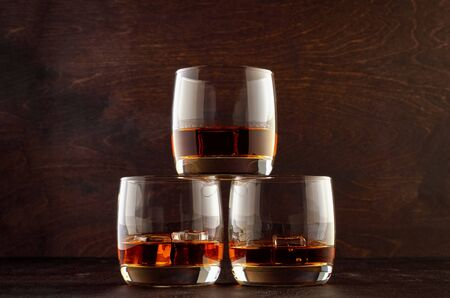 Three glasses of whiskey and ice stand in a pyramid on a wooden table.