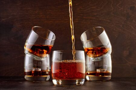 Five glasses of Scotch and ice stand on a wooden table. One glass of whiskey in the foreground and four glasses in the background. Top in a glass filled with whiskey.