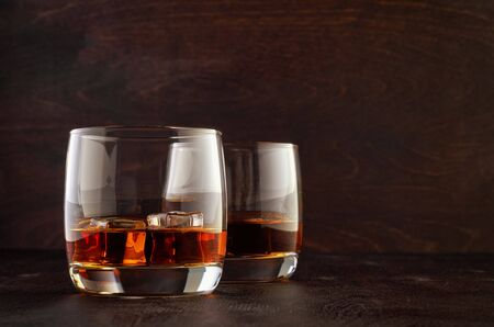 Two glasses of whiskey with ice on the wooden table