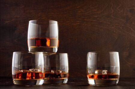 Four glasses of whiskey and ice stand on a wooden table. Three stand in a pyramid, one side by side.