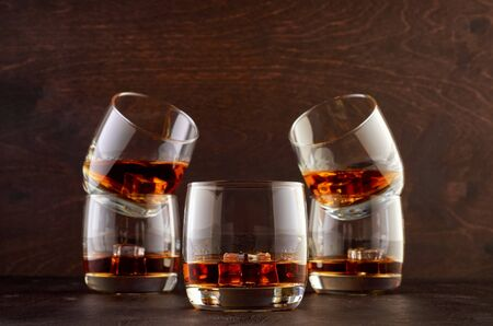 Five glasses of whiskey and ice stand on a wooden table. One glass of whiskey in the foreground and four glasses in the background.