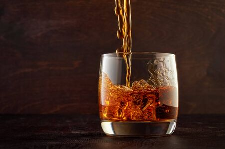 A glass of whiskey on the rocks with a double portion is on the wooden table. Top in a glass filled with whiskey.