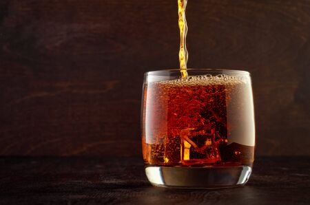 A full glass of whiskey and ice stands on the wooden table. Top in a glass filled with whiskey.