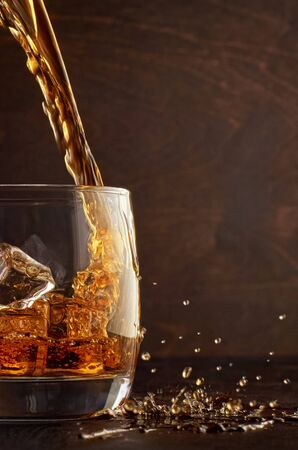 A glass of whiskey with ice on the wooden table. Top in a glass filled with whiskey. Right splashes from the drink. Stok Fotoğraf