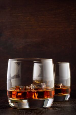 A glass of whiskey with ice on a wooden table Stok Fotoğraf