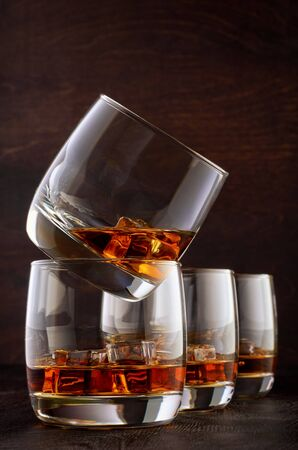 Two glasses of whisky and ice on the wooden table. One stands on top of the other. Two glasses of whisky in the background.