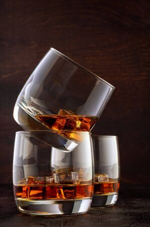 Two glasses of whisky and ice on the wooden table. One stands on top of the other. A glass of whisky in the back. Stok Fotoğraf