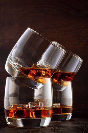 Set of four glasses of whiskey on the wooden table with ice. One glass is on top of the other in pairs.
