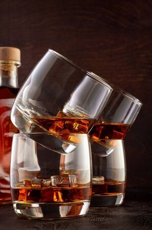Set of four glasses of whiskey on a wooden table with ice. One glass is on top of the other in pairs. In the background, a full bottle of whiskey. Stok Fotoğraf