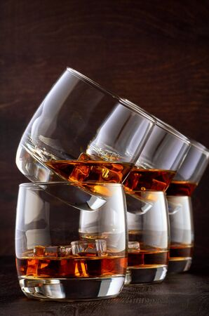 Set of six glasses of whiskey on a wooden table with ice. One glass is on top of the other in pairs.