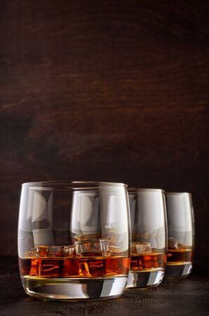 Three glasses of whiskey with ice on the wooden table Stok Fotoğraf