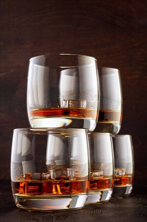 Five glasses of Scotch and ice stand in a pyramid on a wooden table.