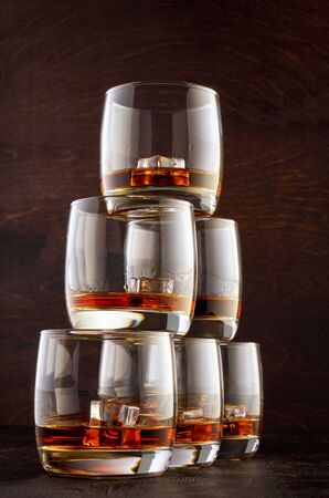 Six glasses of whiskey and ice stand in a pyramid on a wooden table. Stok Fotoğraf