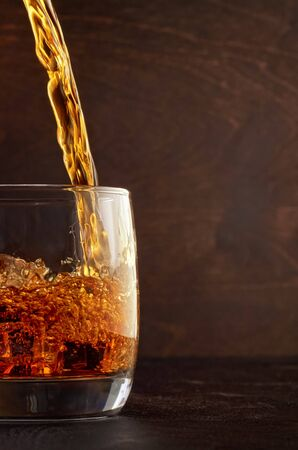 A glass of whiskey and ice on the wooden table. Top in a glass filled with whiskey. Stok Fotoğraf