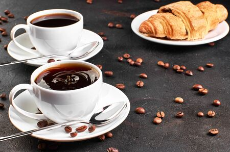 Two cups of coffee on a saucer and coffee beans on a dark background. Croissant in the background. A drop of coffee splashed in the Cup.