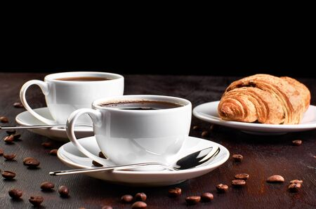 Two cups of coffee in a saucer and a croissant on a dark wooden table. Archivio Fotografico - 131660808