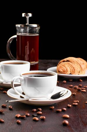 Two cups of coffee in a saucer and coffee beans on a dark wooden table. Croissant and coffeemaker in the background. Archivio Fotografico - 131660810