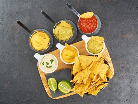 Nachos - yellow corn chips with various sauces in bowls: guacamole, cheese sauce, salsa sauce, on a dark background. Mexican food concept. The view from the top. Stock Photo