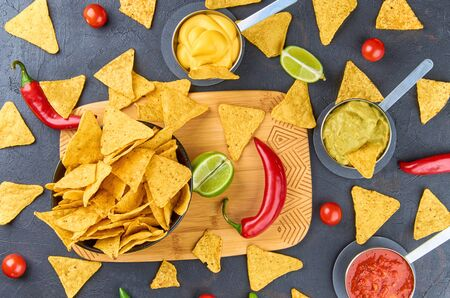 Nachos - yellow corn chips with various sauces in bowls: guacamole, cheese sauce, salsa sauce, on a dark background. Mexican food concept. The view from the top. Stok Fotoğraf